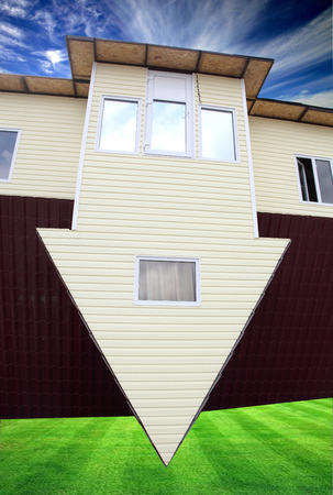 reversing: inverted house on green grass Stock Photo