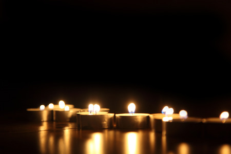 Candles in a row on a gold colored glass table top. photo