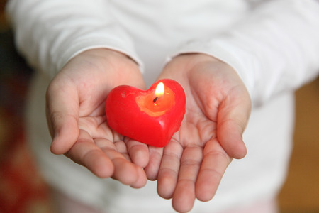 godlike: red candle on the palms of the child Stock Photo