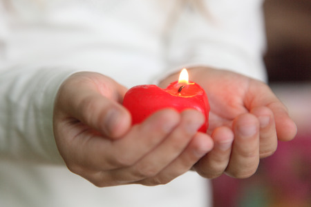 red candle on the palms of the child Stock Photo