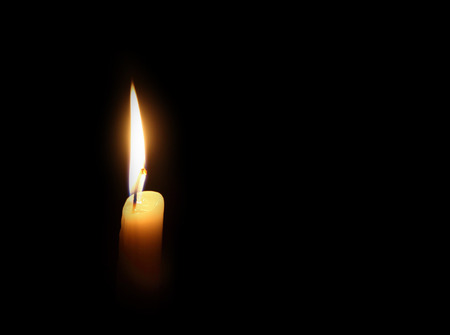vigil: candle burning on a dark background