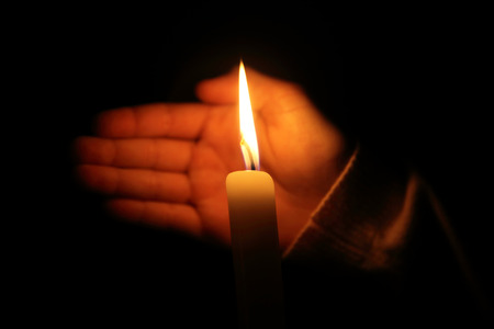 hand protects the flame from a candle burning on a dark background photo