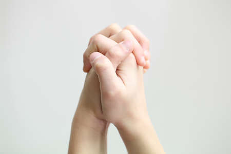 niño orando: dos manos juntas en oración Foto de archivo