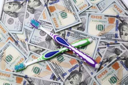 paradontosis: two toothbrushes on the background of dollar bills Stock Photo