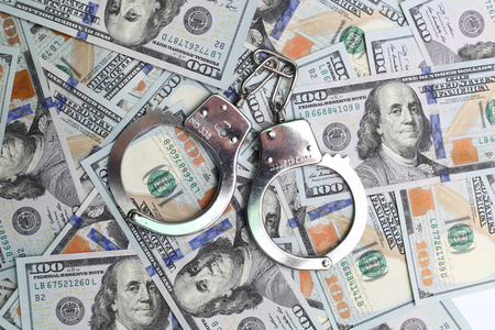 atonement: handcuffs on a pack of dollars