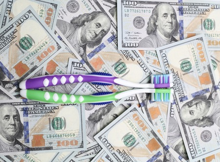 cleaning debt: two toothbrushes on the background of dollar bills Stock Photo