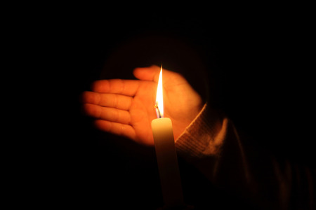 easter candle is burning: hand protects the flame from a candle burning on a dark background