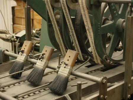 stitching machine: Brushes on ancient stitching machine in publishing house