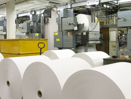 Paper rolls in front of printing press