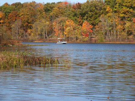 sightseers: Autumn lake with pontoon boat approaching in background