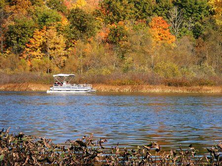sightseers: Pontoon boat on an autumn lake