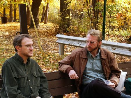 serious guy: men, coworkers, colleagues, males, friends, pals, buddies, chums, bench park, seated lunch, discussion, serious, trees, autumn, foliage, leaves, yellow, jacket, beard, mustache, glasses, talk, listen, chat, adults, two, nature Stock Photo
