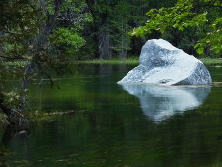 Granite boulder in a placid Yosemite lake at evening photo
