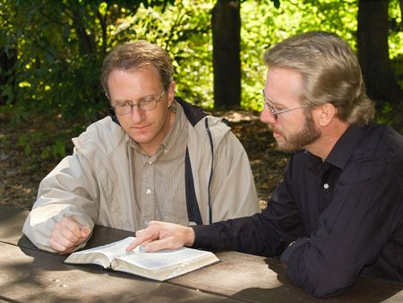 accountability: Two men studying the Bible in an outdoor seting