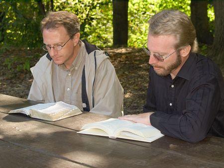 discipleship: Two men reading Bibles at a picnic table