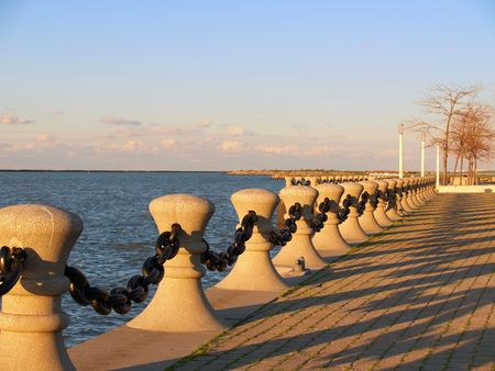 bollards: Harbor edge, with bollards and chain, in evening sunlight