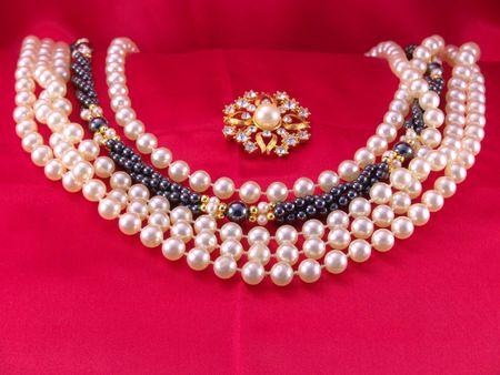 Blanco y negro gargantillas de perlas en rojo tejido con broche de perlas  Foto de archivo - 791308