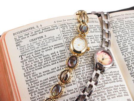 Biblia abierta a Eclesiastés 3, con dos relojes de pulsera, que simboliza el tiempo Foto de archivo