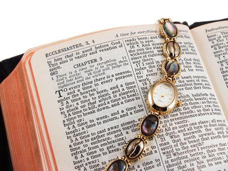 Biblia abierta a Eclesiastés 3 (un tiempo para cada cosa) con reloj de pulsera de oro