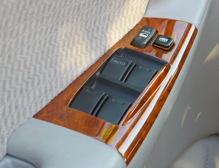 white trim: Door and window controls on interior car door panel