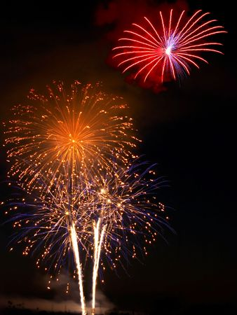 Red, gold, pink, blue fireworks above white rocket trails Stock Photo