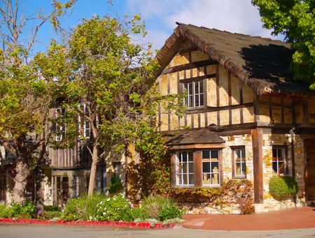 tudor: Tudor-style house with trees and flowers on a quiet street corner Stock Photo