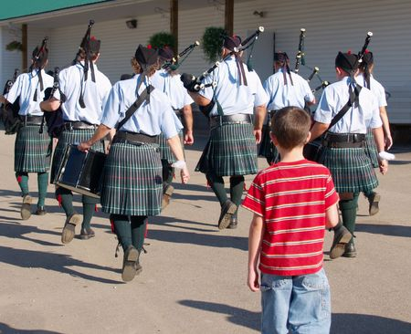 marchers: Young boy following a drum and pipes corps