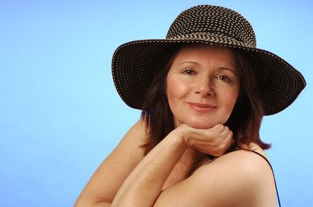 sun hat: Sassy lady in a broad-brimmed sun hat against a plain background