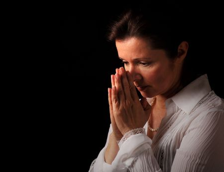 Woman with hands folded in prayer and contemplation