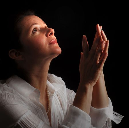 Woman with hands folded in prayer, looking up toward the Light