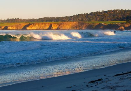 First light of morning sun on breakers and cliffs below Pebble Beach photo