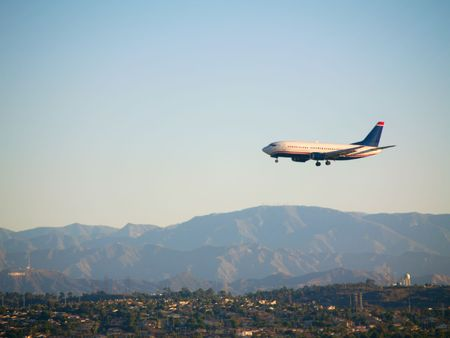 Jetliner landing at Los Angeles in early morning - Hollywod Sign visible at lower left Stock Photo
