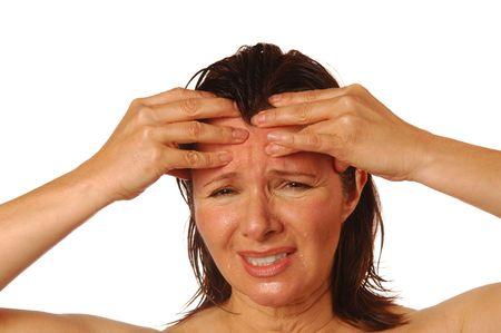 splitting headache: Woman with splitting headache rubbing forehead for relief