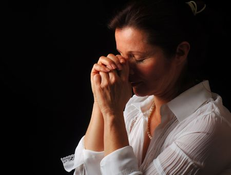 piety: Beautiful woman with eyes closed in fervent prayer Stock Photo