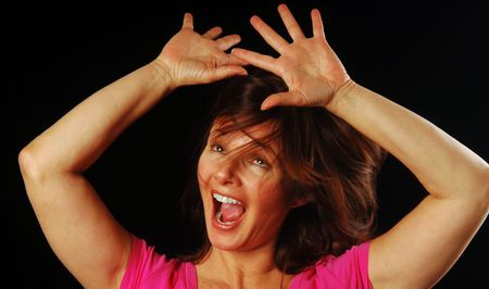 Beautiful woman shaking her head and holding hands up in a moment of wild abandon photo