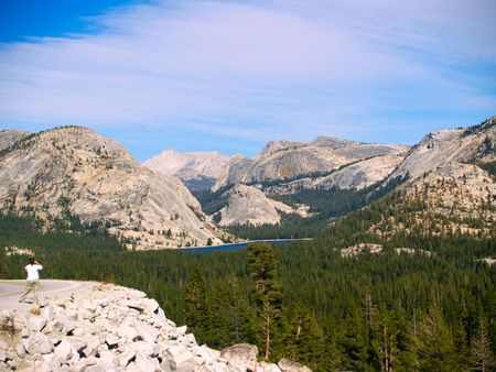 high sierra: Woman photographing Tenaya Lake and High Sierra of Yosemite National Park