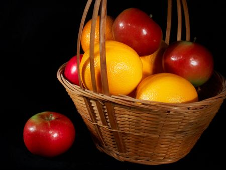 navel orange: A basket of ripe apples and oranges, light painted on a black background