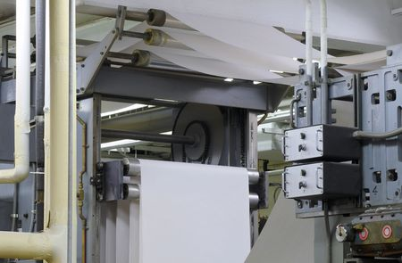 Paper threading its way through a printing press during a press run Stock Photo