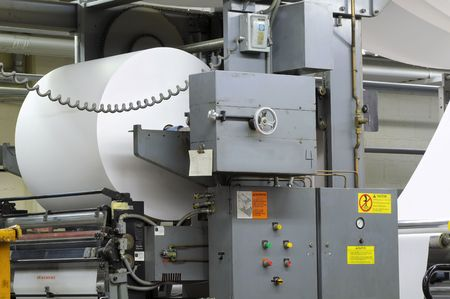 Large roll of paper on a four-web printing press photo