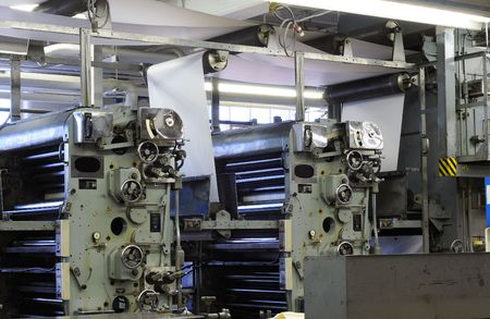Ink rollers and paper on a four-color web printing press photo