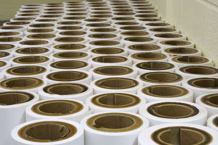 spent: Rows of spent paper rolls from a printing press, waiting for disposal