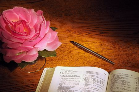 Bible open to Song of Solomon with pen and fabric rose photo