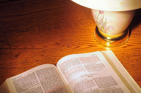 lamp light: Lamp light shining on a Bible, metaphor for the Bibles light to the world Stock Photo
