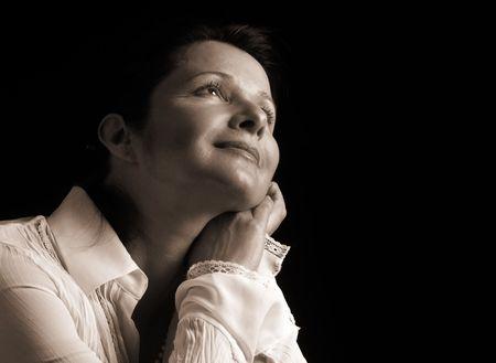contentment: Beautiful woman gazing upward with a feeling of joyful contentment, sepia toned
