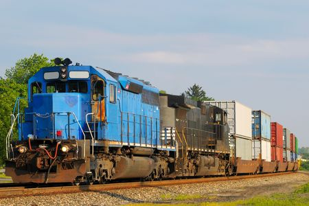 train tracks: Two locomotives pulling a train of container cars