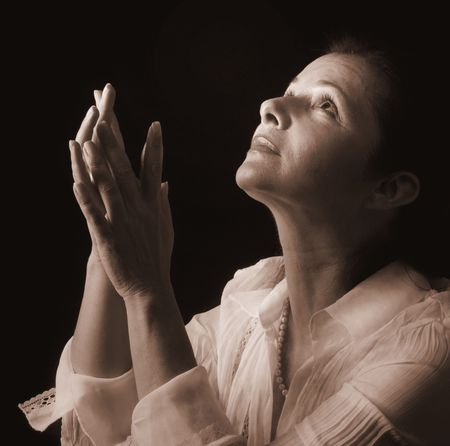 devout: Woman with hands folded in prayer, looking up toward the Light