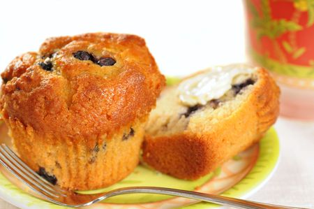 Yummy warm blueberry muffins with a dab of butter and juice photo