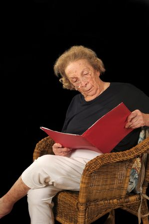 reading material: Elderly lady reading material in a looseleaf folder
