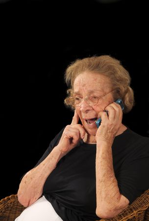 Grandmotherly woman hearing good news on a cell phone photo