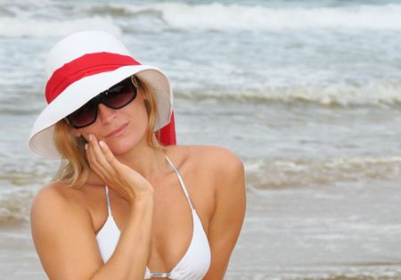 coy: Pretty blonde on a beach in sunglasses and sun hat giving a coy look
